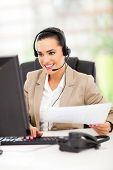 pretty female telemarketer with headphones working in office