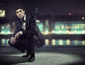 Handsome man over night city background