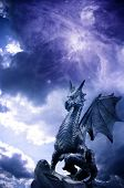 a statue of dragon over stormy magic sky