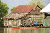 REAM, CAMBODIA - DECEMBER 9: An unidentified man rows his boat through water village on December 9,
