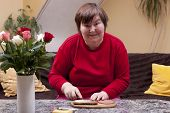 foto of physically handicapped  - Mentally handicapped woman is making up a sandwich - JPG