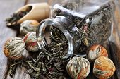 stock photo of tea bag  - Green tea balls with flowers and glass jar with tea on wooden table - JPG
