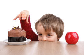picture of cheeky  - Healthy or unhealthy eating little boy choosing between a cake or an apple - JPG