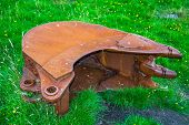 Old rusty excavator shovel in the grass