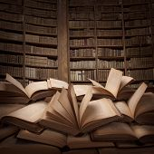 stock photo of wooden table  - Pile of open books on the table - JPG