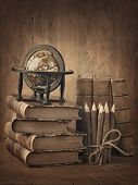 Stack of books and globe on wooden table