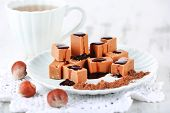 Many toffee on plate and cup of tea on napkin on wooden table