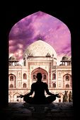 stock photo of padmasana  - Yoga meditation in lotus pose by man silhouette in arch at Humayuns tomb and purple sky background in New Delhi India - JPG