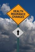 health insurance changes ahead road sign over dark sky with clouds