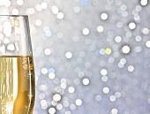 picture of flute  - one flute of golden champagne on silver bokeh background with space for text - JPG