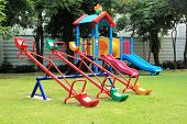 stock photo of seesaw  - Colorful seesaw on a playground in a sunny day - JPG