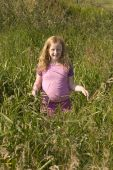Little Girl In Pink Clothes Between High Grass