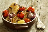 Roasted chicken with tomatoes and garlic in a pan
