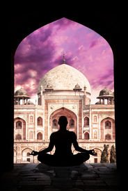 foto of samadhi  - Yoga meditation in lotus pose by man silhouette in arch at Humayuns tomb and purple sky background in New Delhi India - JPG