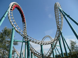 stock photo of amusement park rides  - Rollercoaster in action in amusement park in summer - JPG