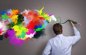 Businessman painting abstract colorful design on gray background concept for  business creativity, imagination and inspiration