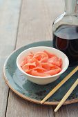 stock photo of zingiber  - Pickled ginger with soy sauce and wooden chopsticks on plate - JPG