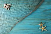 stock photo of fishnet  - Summer holidays background in blue with fishing net ans seashells and a space for advertising - JPG
