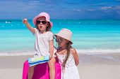 Little adorable girl looking for way with a map and big suitcase on the beach
