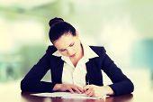 Beautiful attractive corporate lawyer business woman sitting at desk and writing blank paper page