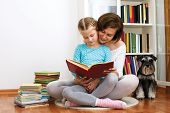 stock photo of schnauzer  - Mom reading a book her little daughter - JPG