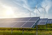 stock photo of environment-friendly  - solar panels and wind generators under blue sky on sunset - JPG