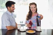 Portrait of a smiling young couple with woman holding out credit card at the coffee shop