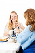 Mother and daughter having a Mother's Day tea party.  Mom is pouring tea.  White background