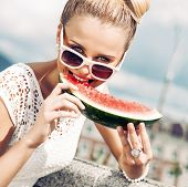 image of bow tie hair  - beautiful young girl with bow tie hair in white summer dress wearing sunglasses bites juicy watermelon - JPG