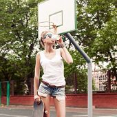 Beautiful Lady In Jeans Shorts With Skateboard And To-go Cup At Sport Court