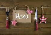 Christmas menu card for restaurants with knife and fork on wooden background with red white checkered stars.