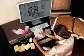 Female interior designer at her workplace. Architectural house plan at computer monitor