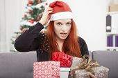 Girl Scratching Head And Holding Christmas Gifts