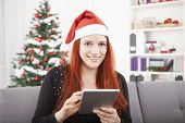Girl Reading Something For Christmas On The Tablet