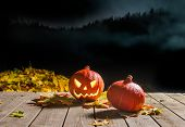 pic of scary haunted  - Carved Halloween pumpkin smiling in the night next to leaves - JPG