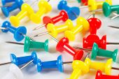 Multicolored office thumbtacks on white desktop closeup