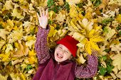 little girl in autumn park lying on leaves