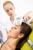 woman having a stimulating facial treatment from a therapist on the table in professional clinic sp