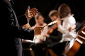 foto of orchestra  - Conductor directing symphony orchestra with performers on background hands close - JPG