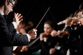 pic of directional  - Conductor directing symphony orchestra with performers on background - JPG