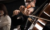 picture of orchestra  - Symphony orchestra performing with cello player hand close - JPG