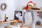 Happy young woman smiling happy having fun with Christmas preparations wearing Santa hat