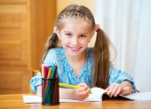 Schoolgirl with colored felt-tip pens in the classroom