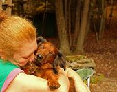 Woman hugging dog in the forest