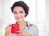 foto of pajamas  - Happy woman holding a cup of coffee in her kitchen wearing pajamas - JPG