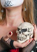 Skull in the hand of blonde girl in mask