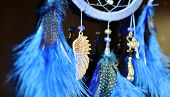 Blue dream catcher hanging on dark background close up with suspension wing