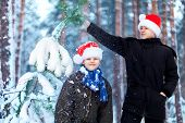 Two Teenagers In Christmas Hats Santa Claus Having Fun In The Snow-covered Forest