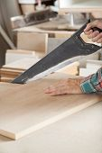 Cropped image of carpenter cutting wooden plank with handsaw at table in workshop