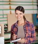 Portrait of confident female carpenter holding pencil and paper in workshop